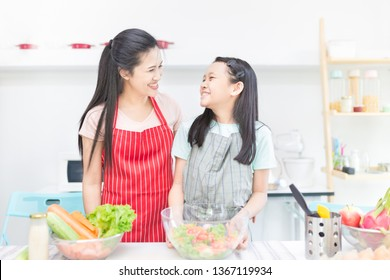 attractive asian children and her mother cooking organic vegetables salad, they feeling happy and smile in family time