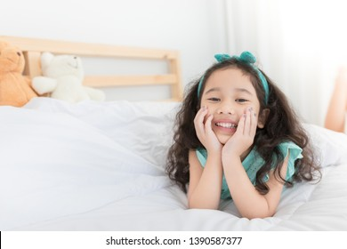 attractive asian children relax on white bedroom, she smiling and feeling happy, she rest chin on her hand, curly hair