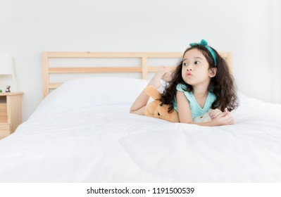 attractive asian children rest on white bed, pucker lips, she feeling happy, curly hair