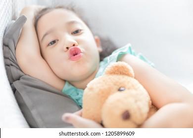 attractive asian children rest on sofa, she hug a bear doll, pucker lips, she feeling happy
