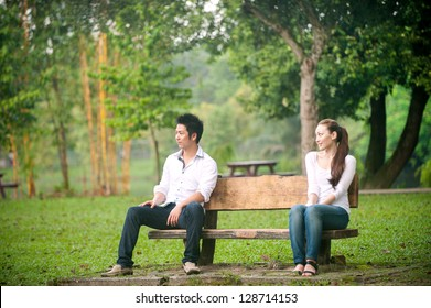 Attractive Asian Couple arguing in park bench