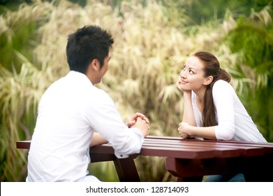 Attractive Asian Couple dating on a bench in park