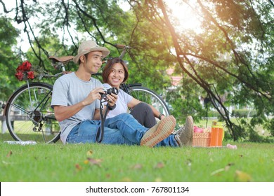 Attractive asian couple dating in the park togetherness relaxation concept