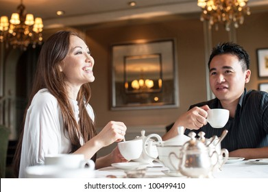 Attractive asian couple enjoying high tea