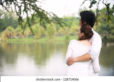 Attractive Asian Couple enjoying lake view in park