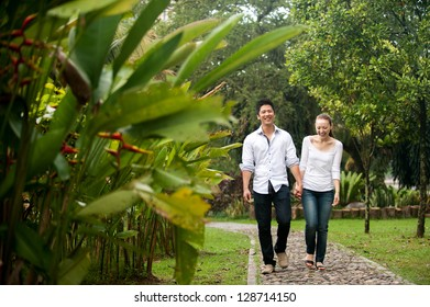Attractive Asian Couple happily walking in park