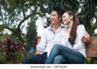 Attractive Asian Couple looking to the side on the bench