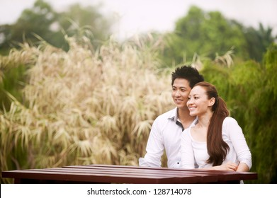 Attractive Asian Couple sitting on a table in park