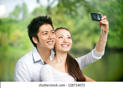 Attractive Asian Couple taking photo in park