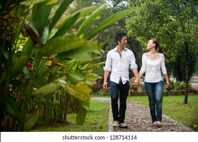 Attractive Asian Couple walking hand in hand in park