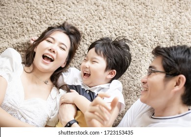 Attractive asian family happy having fun laughing together lying down on carpet floor in house in long weekend