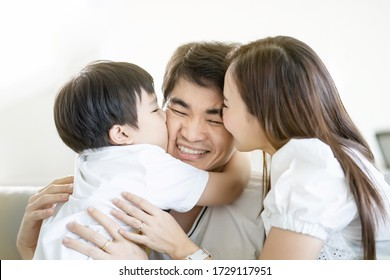 Attractive Asian family happy, mom and kids hug and kiss dad together ,sitting on sofa in living room at home, real people happiness relationship concept.