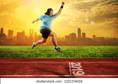 Attractive asian fat man running on running track with 2019 number on the start line. New Year Resolution 2019