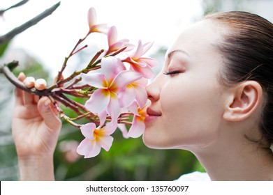 Attractive Asian Female closely smelling a bunch of flower