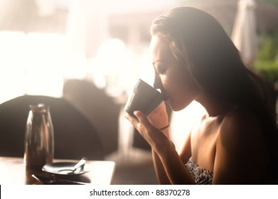 Attractive Asian Female drinking from a cup