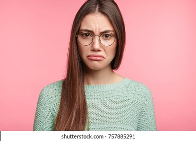 Attractive Asian female has upset look, curves lower lip, being abused by someone, expresses dissatifaction and discontent, frowns face, displeased with results of exam, wants to retake, improve mark