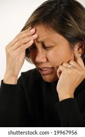 An attractive Asian female with a migraine, headache, or earache.