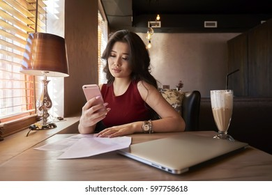 attractive asian female owner of trading corporation making paperwork and checking email waiting for message from marketing experts providing advertising campaign on popular website via smartphone