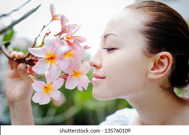 Attractive Asian Female smelling a flower