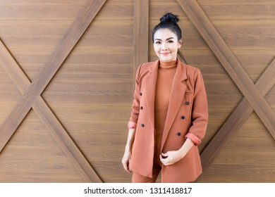 attractive asian female stand on wooden wall, asian woman in brown coat, she feeling happy and smile
