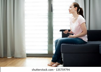 Attractive Asian Female watching tv at home holding a remote