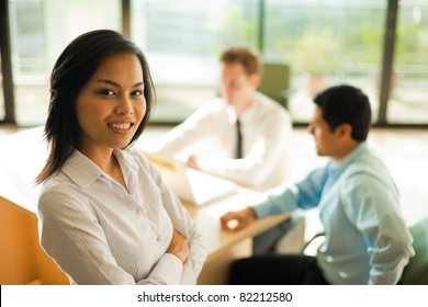 Attractive Asian female with white blouse smiling standing in foreground, looking at the camera during a business meeting, coworkers sitting at desk in background. Horizontal