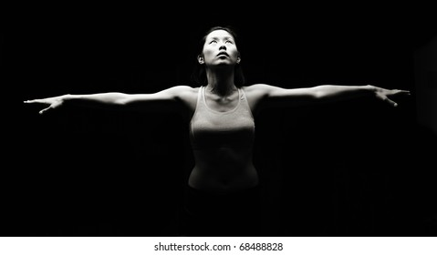 Attractive Asian fitness woman practicing yoga, low key image