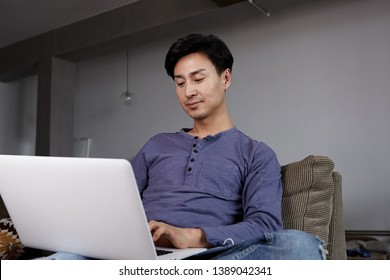Attractive Asian gay Man Working Laptop Home Connecting Networking Concept.