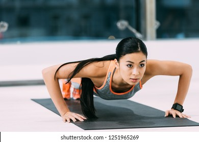 attractive asian girl doing press ups on fitness mat at gym