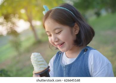 Attractive Asian girl enjoy eating soft ice cream