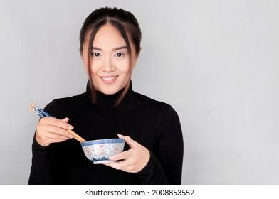 atractiva chica asiática te mira mientras sostiene un tazón chino y palillos