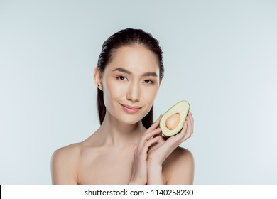 attractive asian girl posing with avocado, isolated on grey