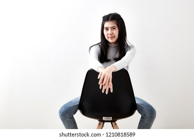 Attractive Asian girl sitting on white modern chair and relax at home. love Valentine's Day - Holiday