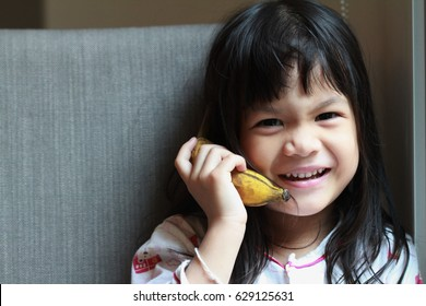 Attractive Asian little girl with natural motion ,make a fake call by using banana ,happy face.Imagination is more important than knowledge.
