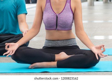Attractive Asian male and female practicing yoga in lotus pose; A young couple doing yoga to meditate their body and soul after work. Two Asian people doing yoga outdoors.