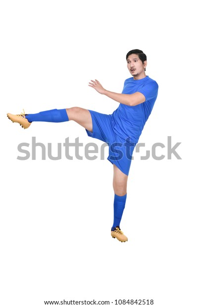 Attractive asian male soccer player kicking the ball isolated over white background