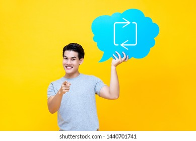 Attractive Asian man holding speech bubble with retweet sign isolated on yellow studio background