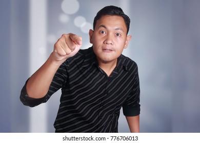 Attractive Asian man shows cynical unhappy angry intimidating facial expression pointing forward, looking at camera