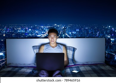Attractive Asian man using laptop computer on his bed at night doing hard work and blue light reflection from computer screen