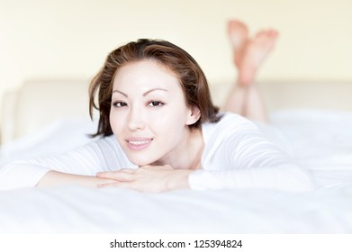 Attractive Asian Mixed Woman in Bed Smiling with crossed legs