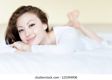 Attractive Asian Mixed Woman in Bed Smilling