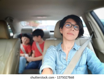 Attractive asian mom driving a car in the city with her kids at the back seat. Driving safety Concept, mom lifestyle, city life.
