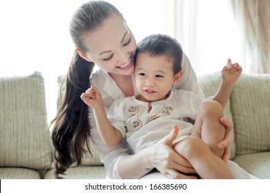 Attractive asian mother playing with smiling son