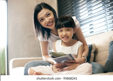 Attractive asian mother reading with her daughter