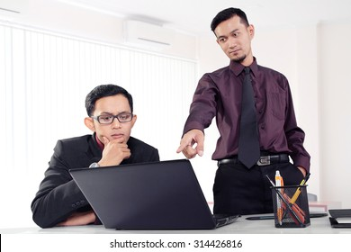 Attractive Asian office worker showing something to his co-worker on a laptop at their office workplace
