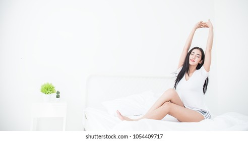 Attractive asian sexy woman awaking on the bed (sleep). Young beautiful girl stretching her arms in the morning relax peaceful concept.