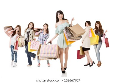 Attractive asian shopping women, with girl in front, walk and look at the camera. Group full length portrait. Isolated on white background.