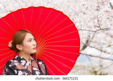 attractive asian woman and cherry tree in a kimono