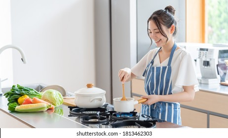 attractive asian woman cooking at kitchen