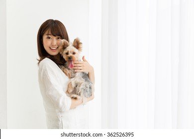 attractive asian woman with dog in the room